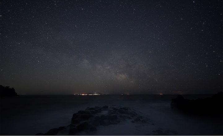 Foto van sterrenhemel boven de zee met de Melkweg