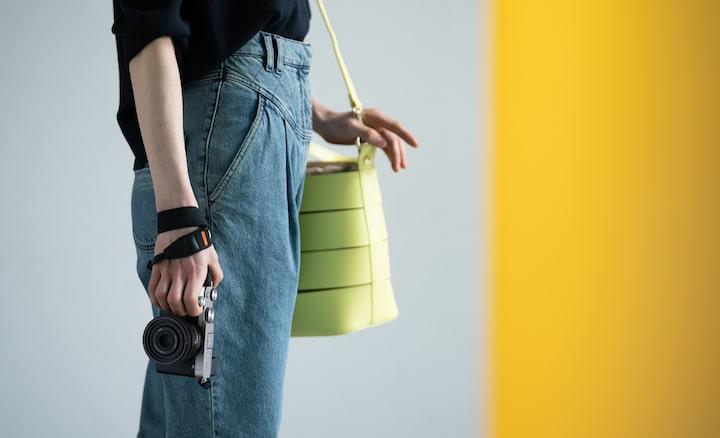 Afbeelding van een persoon die staat en een camera vasthoudt